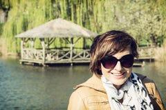 Jonge vrouwenglimlachen op het meer door de lentevakantie Royalty-vrije Stock Foto's
