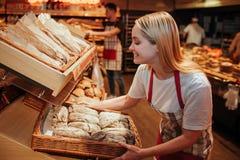 Jonge vrouwengreep bakset met vers brood in kruidenierswinkelopslag Zij zette het op plank en glimlach Smakelijk en delisious wor stock foto's