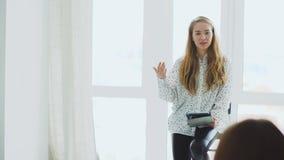Jonge vrouwengrimeur die in conferentie spreken Het leerprogramma van de studiomake-up stock video