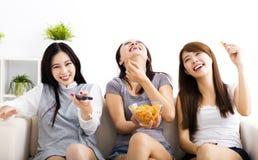 jonge vrouwengroep die snacks eten en op TV letten Stock Fotografie