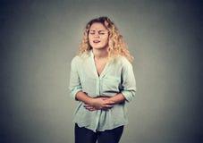 Jonge vrouwenhanden op maag die slechte pijnenpijn hebben royalty-vrije stock afbeelding