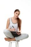 Jonge vrouwenholding sketchbook en pen Stock Foto's