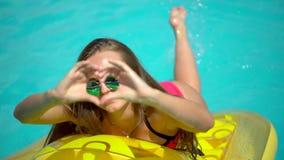 Jonge vrouwenjaren '20 die dichtbij pool bij de zomervakantie leggen en worden ontspannen Bikinimeisje zonnebaden die op opblaasb stock videobeelden