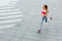 Jonge vrouwenjogging in de ruimte van het stadsexemplaar Stock Afbeelding