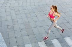 Jonge vrouwenjogging in de ruimte van het stadsexemplaar Stock Fotografie