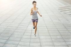 Jonge vrouwenjogging in de ruimte van het stadsexemplaar Stock Foto