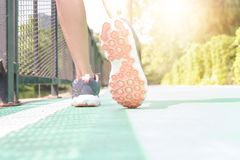 Jonge vrouwenjogging in het park in de ochtend onder warme sunlig stock afbeeldingen