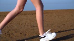 Jonge vrouwenjogging langs een zandig strand stock video