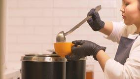 Jonge vrouwenkok die hete soep van steelpan gieten in kom voor lunch in restaurant stock footage