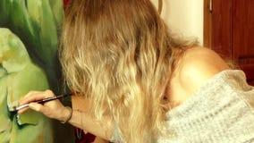Jonge vrouwenkunstenaar die een grote realistische artisjok schilderen stock videobeelden