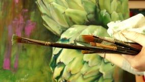 Jonge vrouwenkunstenaar die in een studio werken die een artisjok schilderen stock videobeelden