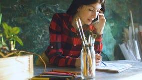 Jonge vrouwenkunstenaar die scetch op document notitieboekje met potlood en sprekende telefoon binnen schilderen stock fotografie