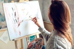Jonge vrouwenkunstenaar die thuis creatief abstract beeld schilderen Stock Foto