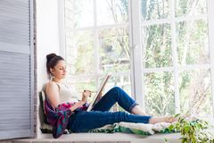 Jonge vrouwenkunstenaar die thuis schilderen stock afbeelding