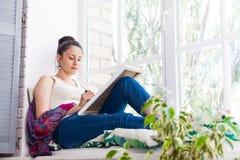 Jonge vrouwenkunstenaar die thuis schilderen stock foto
