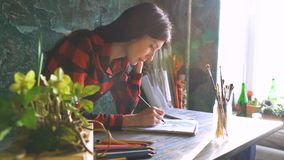 Jonge vrouwenkunstenaar het schilderen schets op document notitieboekje met potlood Heldere zongloed van venster stock afbeeldingen