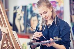 Jonge Vrouwenkunstenaar Working On Painting in Studio Selectieve nadruk op voorgrond royalty-vrije stock foto