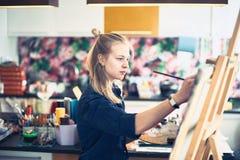 Jonge Vrouwenkunstenaar Working On Painting in Studio Selectieve nadruk op voorgrond stock foto