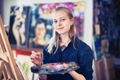 Jonge Vrouwenkunstenaar Working On Painting in Studio Selectieve nadruk op voorgrond royalty-vrije stock fotografie