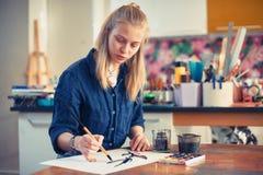 Jonge Vrouwenkunstenaar Working On Painting in Studio Selectieve nadruk op voorgrond royalty-vrije stock afbeelding