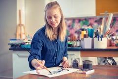 Jonge Vrouwenkunstenaar Working On Painting in Studio Selectieve nadruk op voorgrond stock afbeeldingen