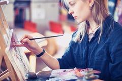 Jonge Vrouwenkunstenaar Working On Painting in Studio Selectieve nadruk op voorgrond royalty-vrije stock afbeeldingen