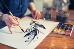 Jonge Vrouwenkunstenaar Working On Painting in Studio Selectieve nadruk op voorgrond stock foto's