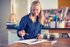 Jonge Vrouwenkunstenaar Working On Painting in Studio Selectieve nadruk op voorgrond royalty-vrije stock foto's