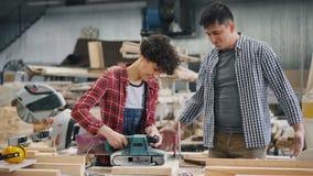Jonge vrouwenleerling die elektrisch poetsmiddel in houten workshop leren te gebruiken stock footage