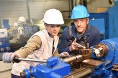 Jonge vrouwenleerling die het metallurgische werk leren stock foto