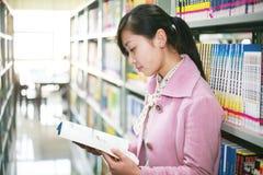 Jonge vrouwenlezing in bibliotheek Stock Foto's