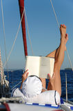 Jonge vrouwenlezing en het zonnebaden op zeilboot Stock Foto