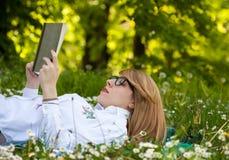 Jonge vrouwenlezing in het park Stock Foto