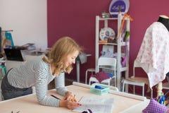 Jonge vrouwennaaister die patroon op stof met kleermakerskrijt maken Meisje die met een naaiend patroon werken Hobby het naaien a Stock Foto
