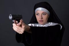 Jonge vrouwennon die met kanon over grijs schieten Stock Afbeelding
