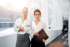 Jonge vrouwenondernemer die op collega's in bureaubinnenland wachten terwijl haar secretaresse die zich dichtbij met omslagdocume Stock Foto's