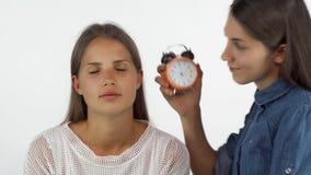 Jonge vrouwenontwaken haar slaperige vriend met een wekker stock footage