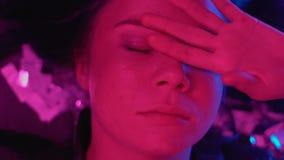 Jonge vrouwenontwaken onder confettien, die aan kater na partij lijden stock footage