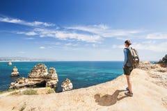 Jonge vrouwenreiziger die het overzees in de stad van Lagos, Algarve gebied, Portugal bekijken reis en actief levensstijlconcept royalty-vrije stock foto