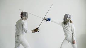 Jonge vrouwenschermer die het schermen binnen opleiding met trainer in witte studio hebben stock foto