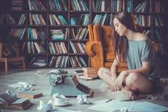 Jonge vrouwenschrijver in bibliotheek thuis creatief beroep geen inspiratie stock afbeeldingen