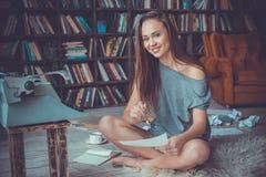 Jonge vrouwenschrijver die in bibliotheek thuis creatief beroep camera het glimlachen kijken stock foto's