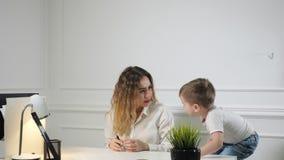 Jonge vrouwensecretaresse met haar weinig zoon in de werkplaats in bureau Werkende moeder stock video