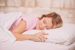 Jonge vrouwenslaap in bed Stock Foto's