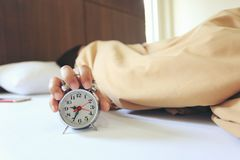 Jonge vrouwenslaap in de slaapkamer met Handvat de wekker in de ochtend, Gezondheidsconcept stock foto