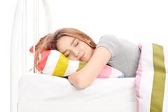 Jonge vrouwenslaap in een comfortabel bed Stock Afbeeldingen
