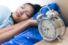 Jonge vrouwenslaap in nachtjapon stock afbeelding
