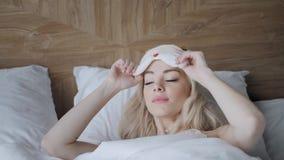 Jonge vrouwenslaap op comfortabel bed in een masker voor slaap Blinddoek op oog Ochtend in hotelruimte Wit hoofdkussen en stock footage