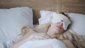 Jonge vrouwenslaap op comfortabel bed in een masker voor slaap Blinddoek op oog Ochtend in hotelruimte Wit hoofdkussen en stock videobeelden