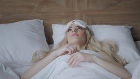 Jonge vrouwenslaap op comfortabel bed in een masker voor slaap Blinddoek op oog Ochtend in hotelruimte Wit hoofdkussen en stock video